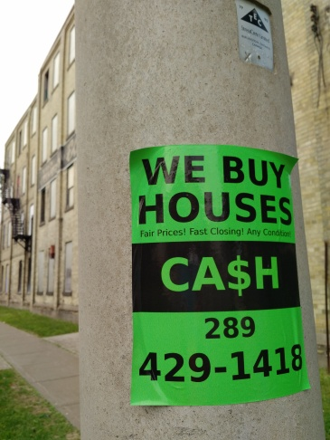 we buy houses sign on a hydro pole in midtown kw