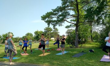 a group of 15 people in tree pose during yoga in the park at Uniroyal Goodrich Park, Kitchener