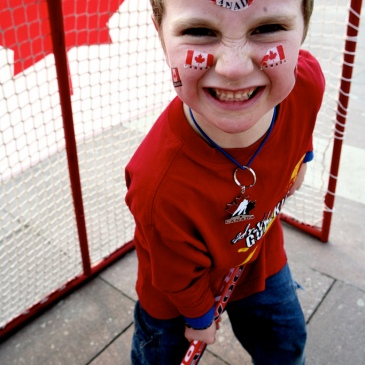 child smiling in front of a hockey net