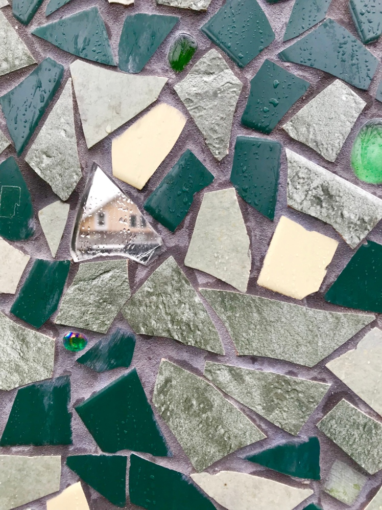Mosaic tiles with house reflection in mirrored piece